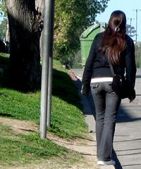 Woman standing on curb, facing downhill, about to step off