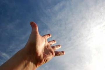 a left hand reaching towards the sun